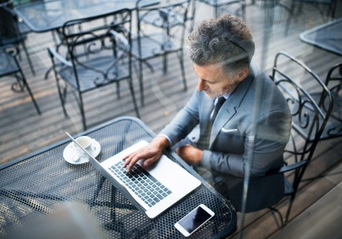 Mature businessman with laptop outside a cafe.